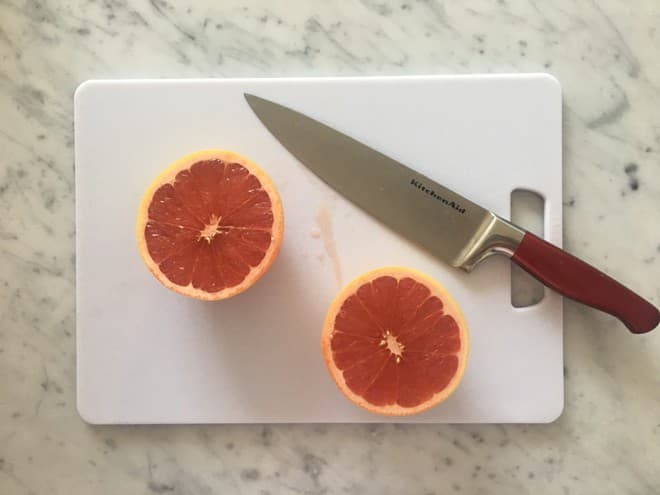 Next, you're going to squeeze out the fresh grapefruit and add to the mint mixture. Make sure to save some extra pieces of grapefruit to add to your trays to add some flair to your popsicles.
